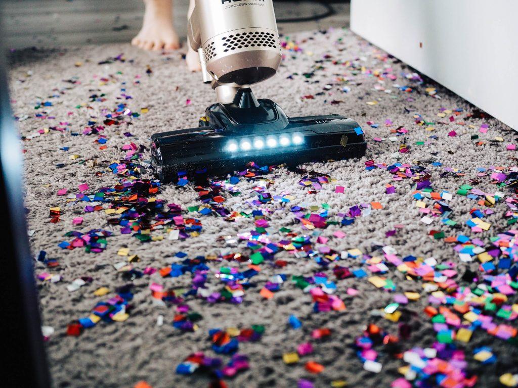 kolorowe konfetii porozrzucane na szarym mięsistym dywanie jako alegoria spor dermatofitów. odkurzacz zbiera konfetii.